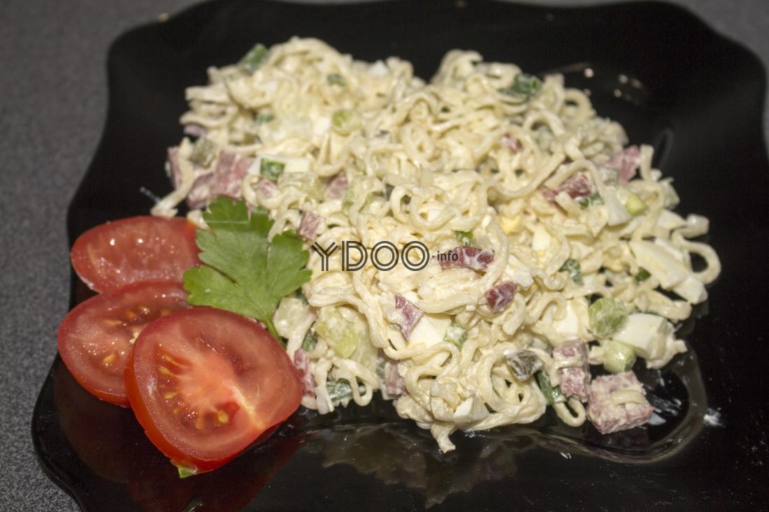 салат из лапши быстрого приготовления, украшенный помидорми и листиком петрушки