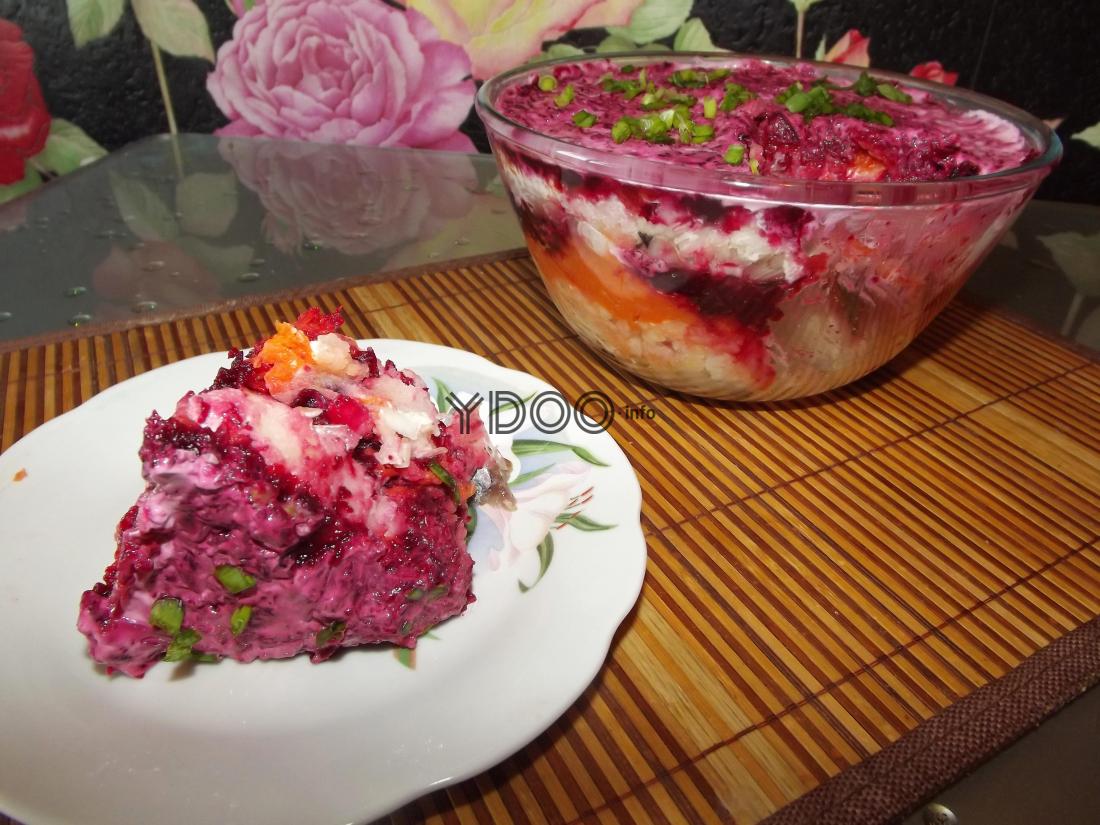 скумбрия под шубой в порционной тарелке, рядом на столе миска с салатом