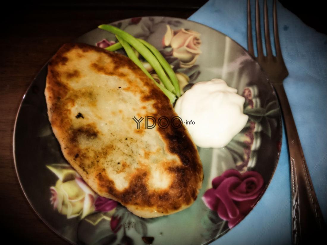 зраза картофельная с грибами в блюдце со сметаной и зеленым луком