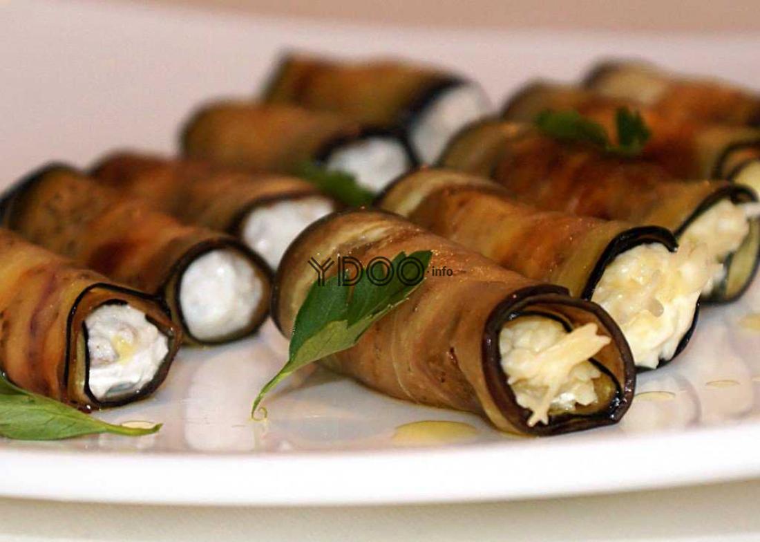 рулетики из баклажанов с начинкой из сыра и чеснока, украшенные свежими листочками петрушки