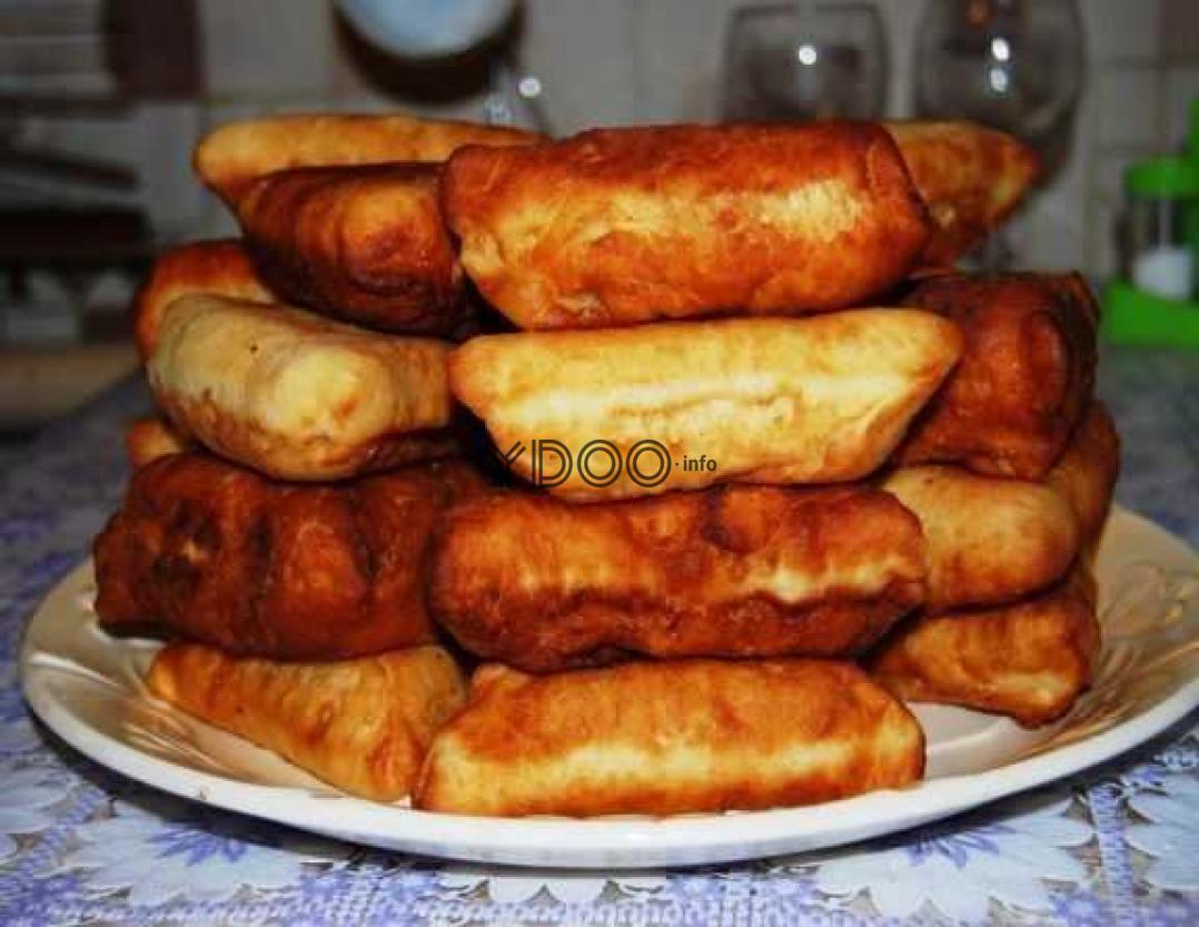 беляши треугольной формы с куриным фаршем, сложенные стопкой, лежат на большом блюде
