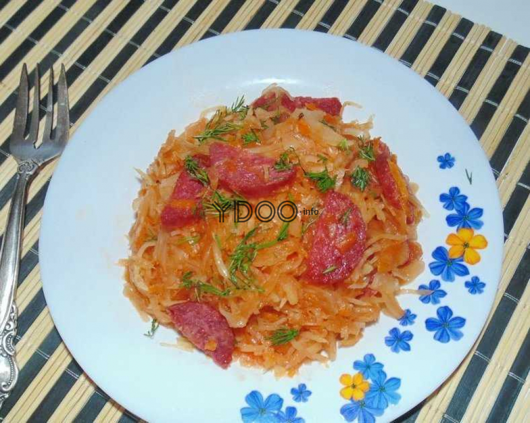 бигус с колбасой в белой тарелке с синими и желтыми цветочками, рядом лежит вилка