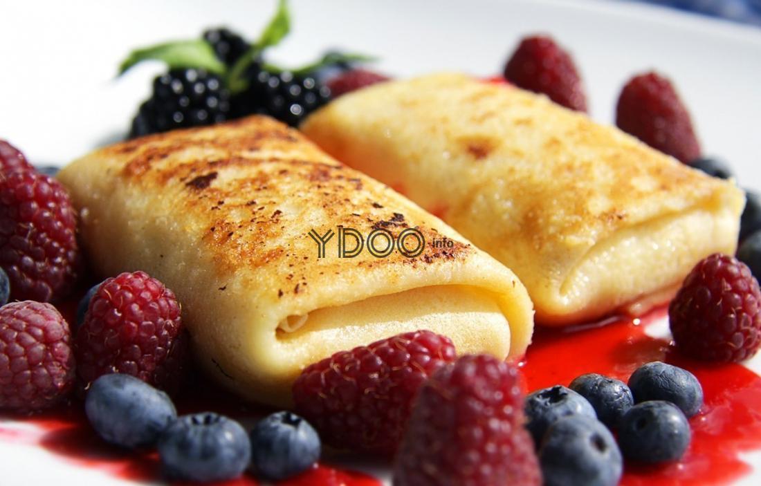 два жареные блина с маскарпоне внутри с лесными ягодами на белой плоской тарелке