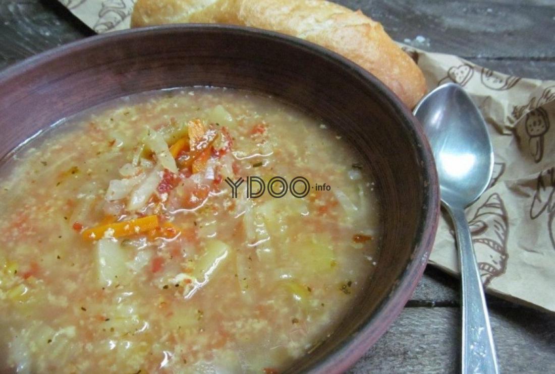 борщ из пекинской капусты, морковки, картошки и специй в глубокой коричневой тарелке на столе, рядом ложка и ломтик белого хлеба