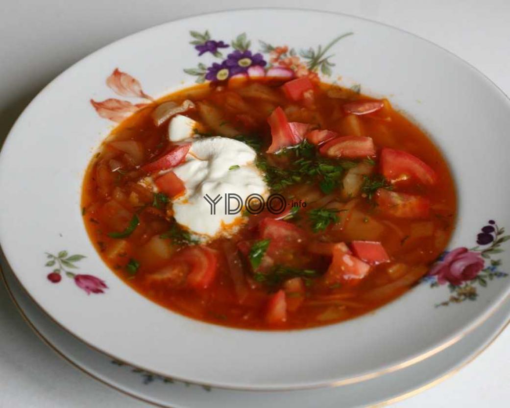 борщ со свежими помидорами в тарелке, заправленный сметаной