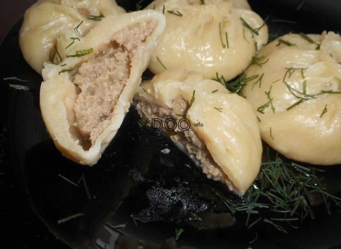 паровые бурятские позы с мясным фаршем, посыпанные рубленой зеленью, на черной тарелке