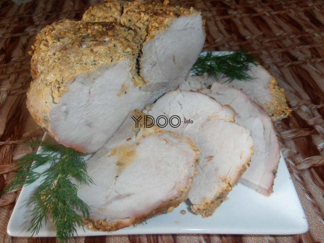 нарезанный кусочек буженины из свинины со специями на белой плоской тарелке с веточками укропа на столе, застеленном скатертью