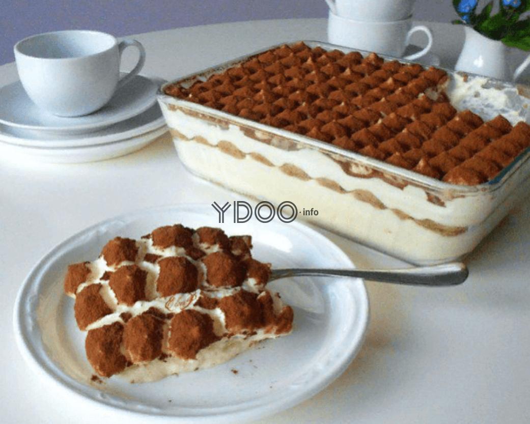 кусочек домашнего классического тирамису в тарелочке с чайной ложкой, на фоне прямоугольная стеклянная форма с остальным тортом, пустая чайная чашка на блюдце