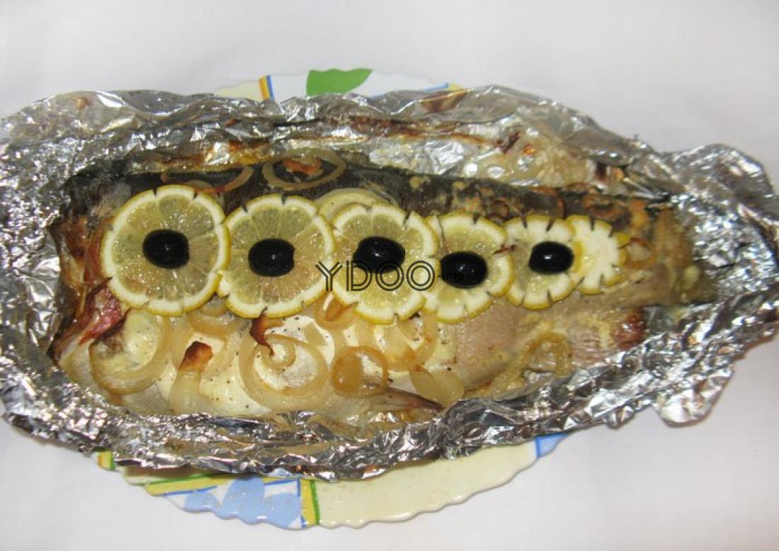 запеченная форель с луком, кусочками лимона и маслинами на тарелке, застеленной фольгой
