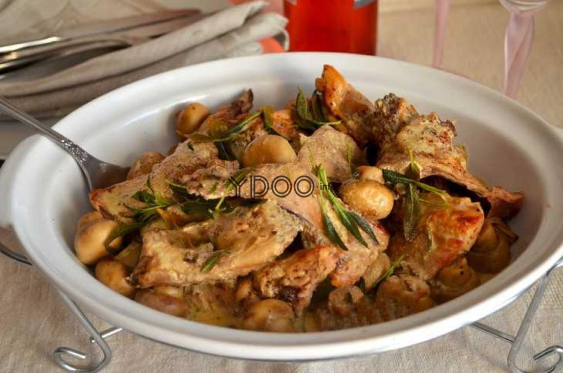 фрикасе из кролика с шампиньонами в сливочном соусе в овальном белом блюде, сверху мясо присыпано листьями шалфея