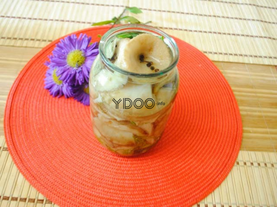 соленые грузди в стеклянной банке с горошинами перца на красной салфетке на столе, застеленном деревянным ковриком