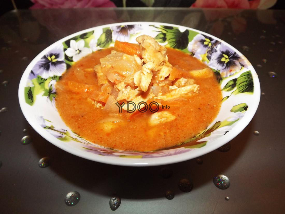 гуляш из курицы с томатной подливкой в тарелке на кухонном столе