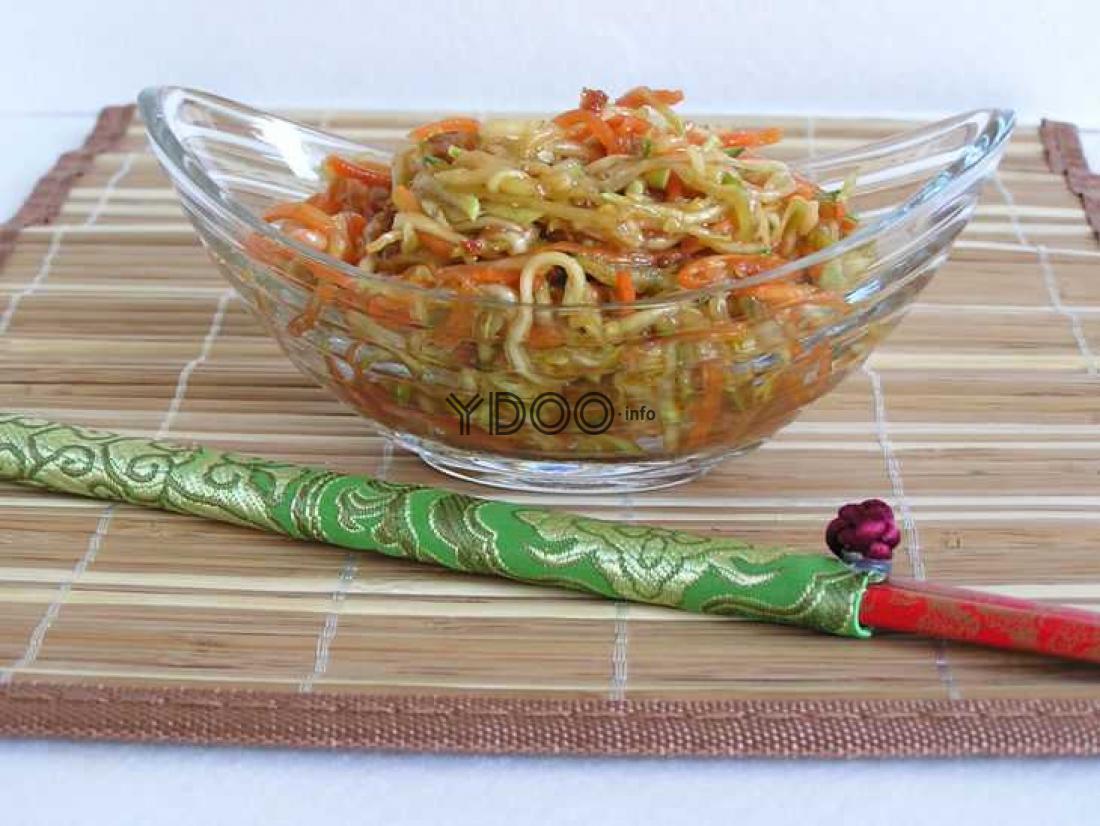 хе из кабачков в стеклянной салатнице, стоящей на бамбуковом коврике, рядом лежат палочки для еды