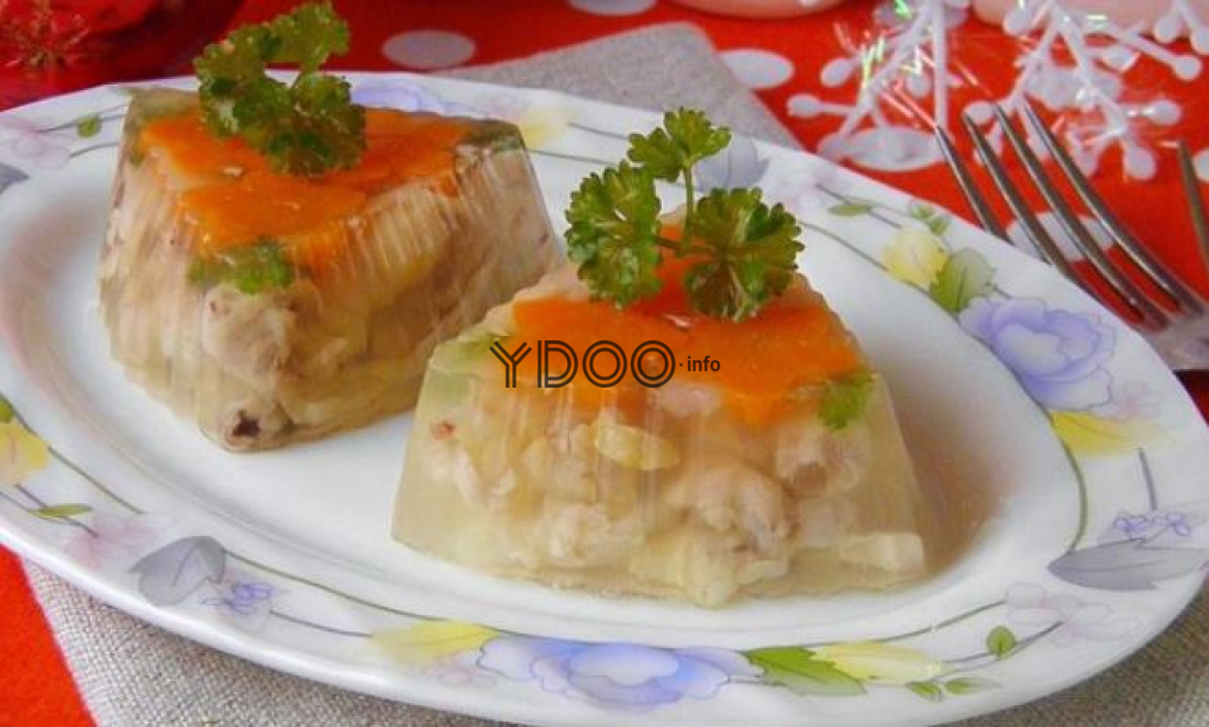 тарелочка с двумя порциями холодца из куриных лапок, украшенными свежей зеленью