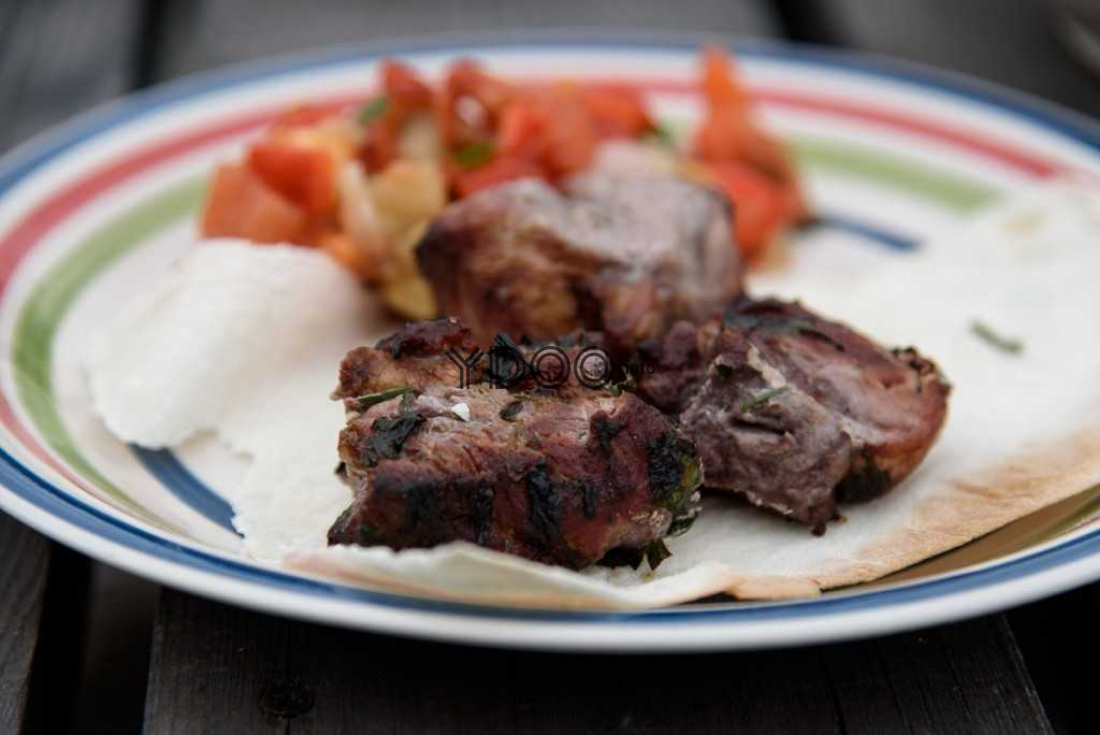 хоровац из свинины на тонком лаваше, рядом овощи на тарелке