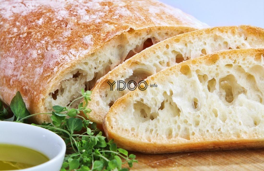 нарезанный итальянский хлеб на деревянной разделочной доске с зеленью