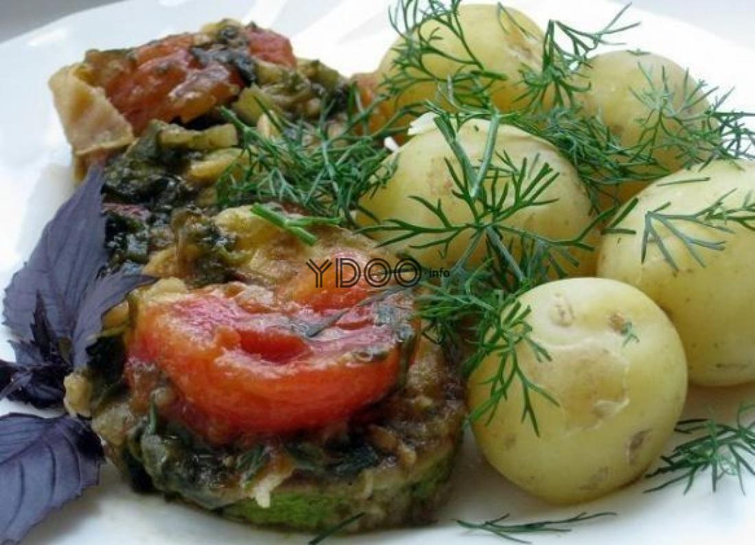 жареные кабачки по-гречески с помидорами и зеленью с отварными картофелинами на белой тарелке