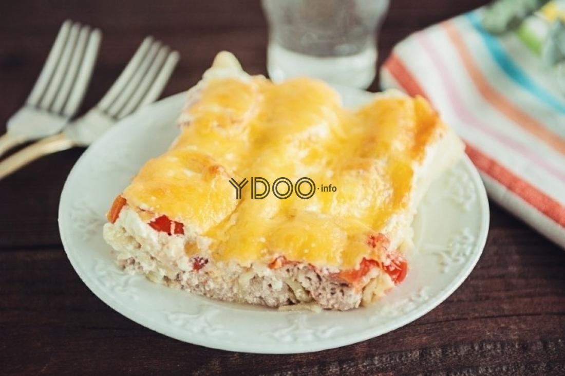 каннеллони с фаршем, помидорами и сыром на белой круглой тарелке на столе