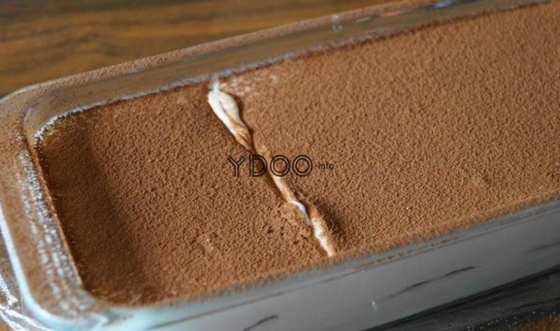 карамельный тирамису, присыпанный тертым шоколадом, в прозрачной стеклянной посуде на столе