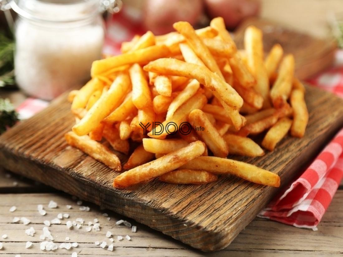 жареный картофель фри на деревянной разделочной доске на столе, прикрытом полотенцем, рядом рассыпаны крупинки соли