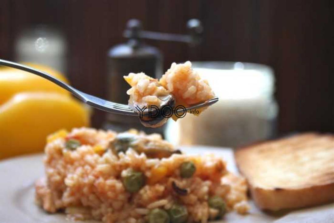 классическая паэлья с морепродуктами на тарелке, рядом лежит гренка, паэлья на вилке