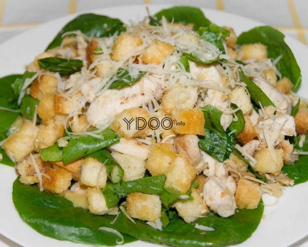 классический салат Цезарь с курицей, поданый на листьях салата романо