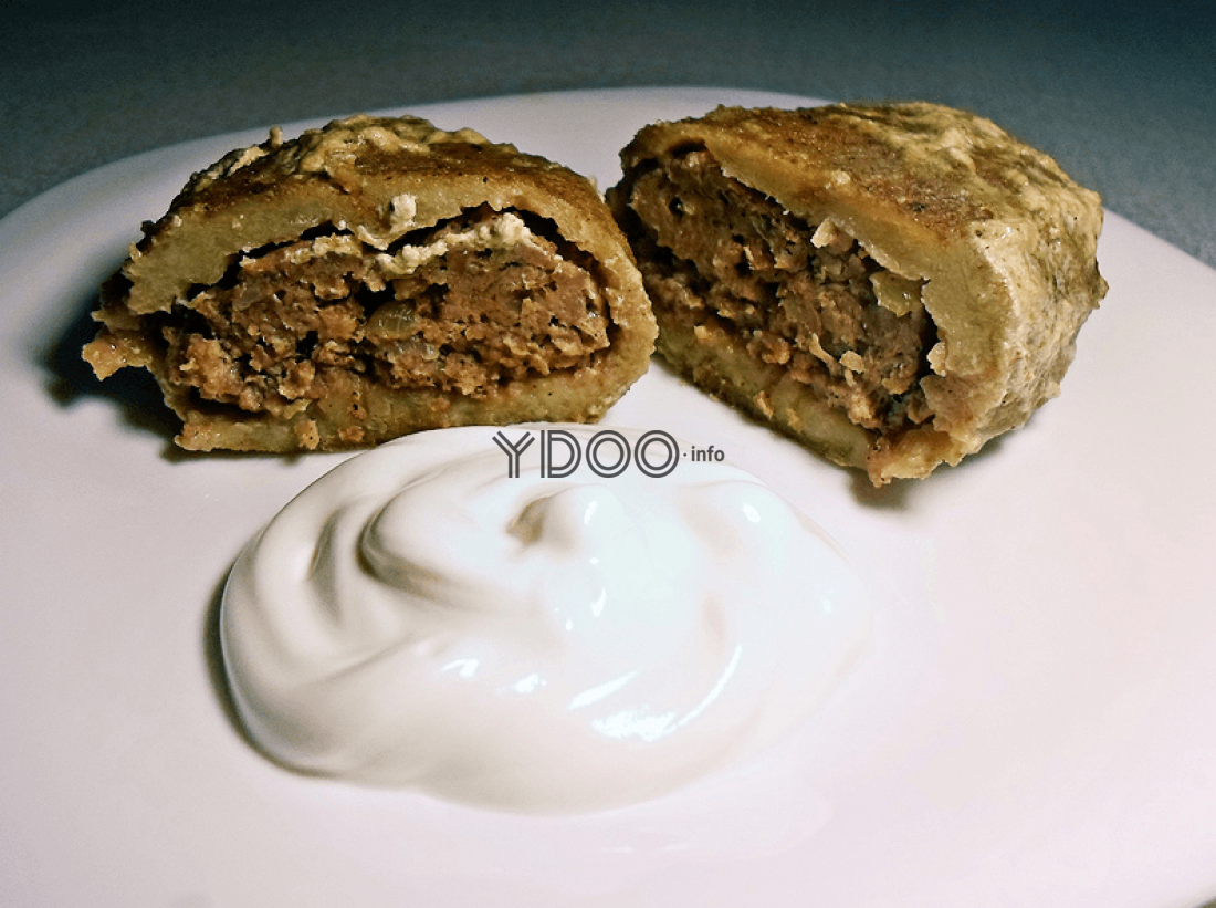 колдуны из картофеля с фаршем на белой круглой тарелке со сметаной