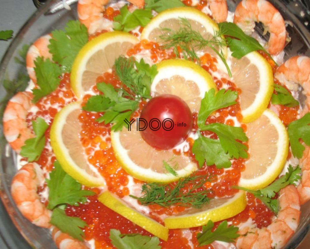 салат креветки под шубой, украшенный дольками лимона, свежей зеленью и красной икрой