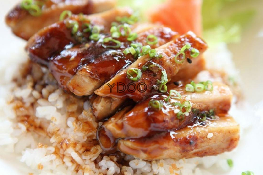 курица терияки в соусе, посыпанная измельченным зеленым луком, лежит на выреном рисе
