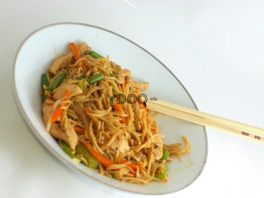 лапша, перемешенная с тертой морковью, жареными кусочками куриного филе, на белой тарелке с китайскими палочками на столе