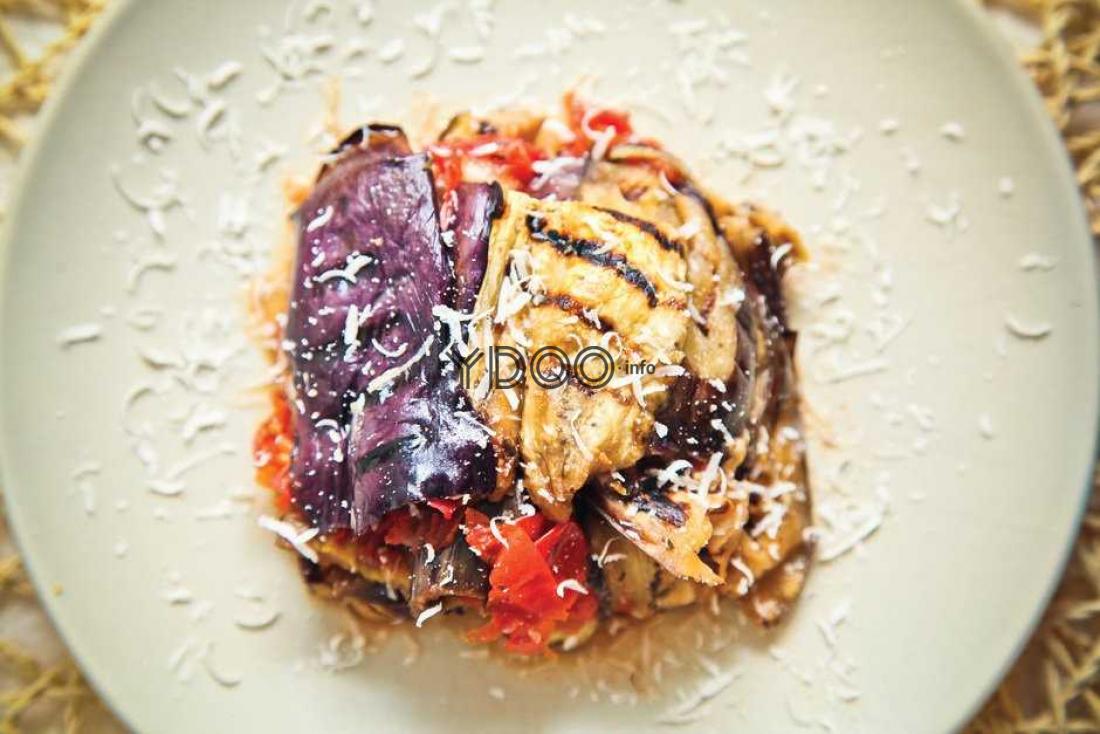 лазанья с баклажанами, припущенными на гриле, помидорами черри, зеленью, сверху блюдо украшено тертым сыром