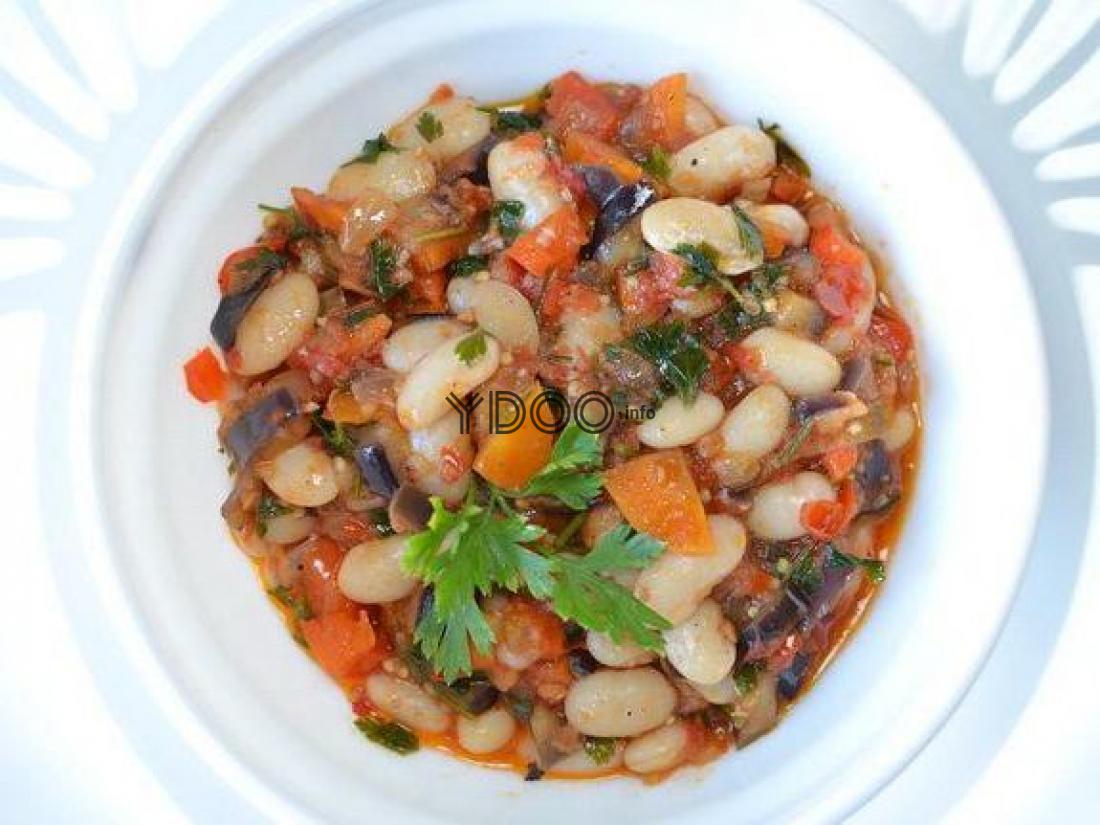 лобио из белой фасоли, баклажанов, моркови томатов с листиками петрушки в белой тарелке на столе