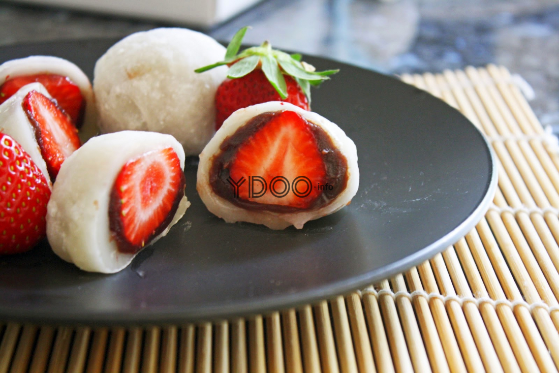 разрезанные японские моти с клубникой, покрытой тестом и шоколадно-ореховой пастой, на черной тарелке на столе, застеленном деревянным ковриком
