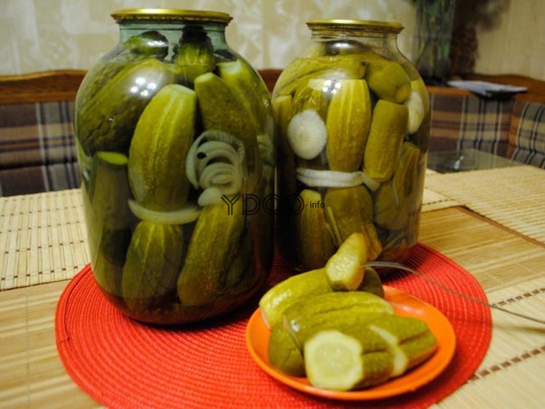 маринованные по-болгарски огурцы с репчатым луком в двух стеклянных бутылях и в красной миске с вилкой на столе, покрытом деревянным ковриком