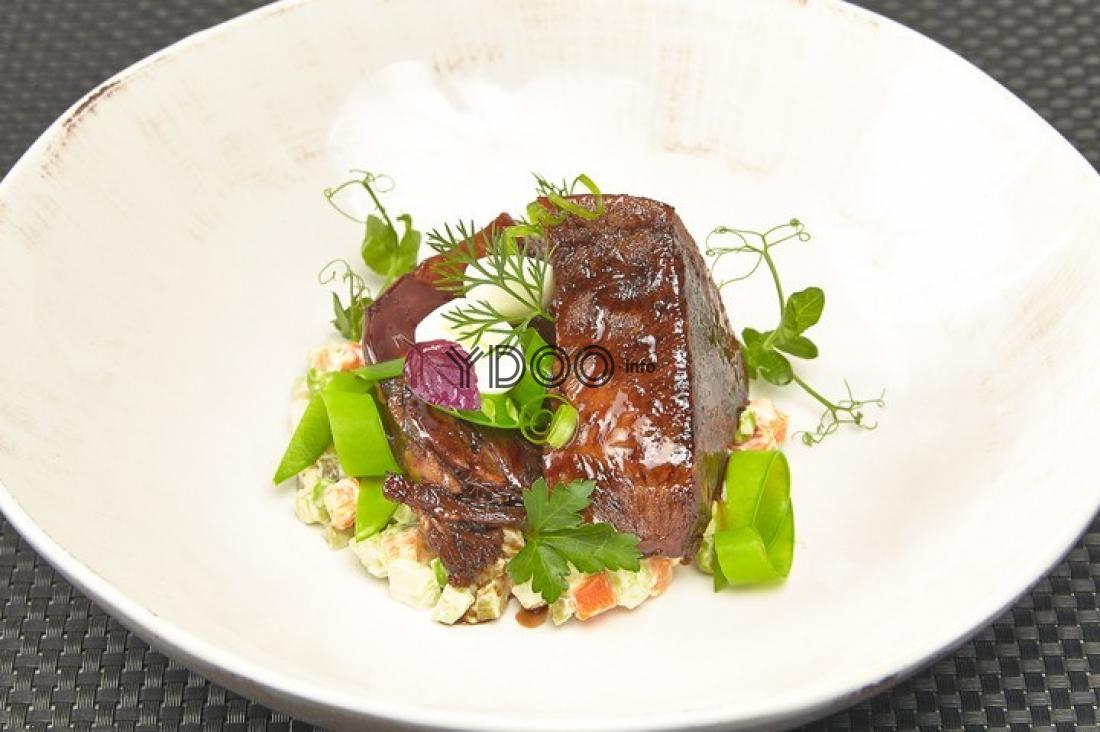 на белой круглой тарелке лежит порция классического оливье с языком, украшенного перепелиными яйцами, веточками укропа, микро-грином и свежей зеленью