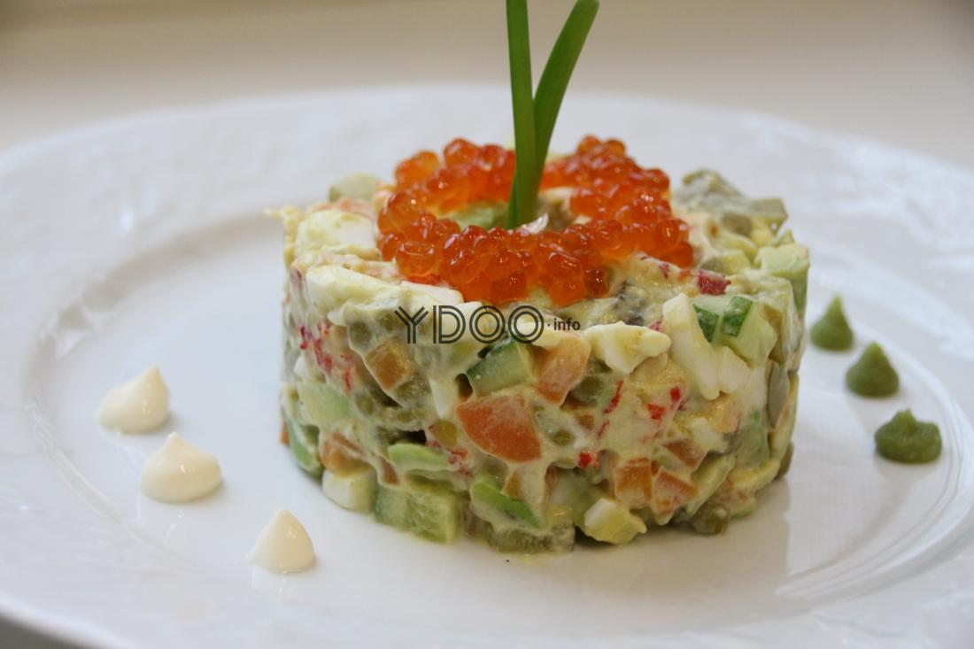 оливье с лососем, сверху украшенный красной икрой и перышками зеленого лука