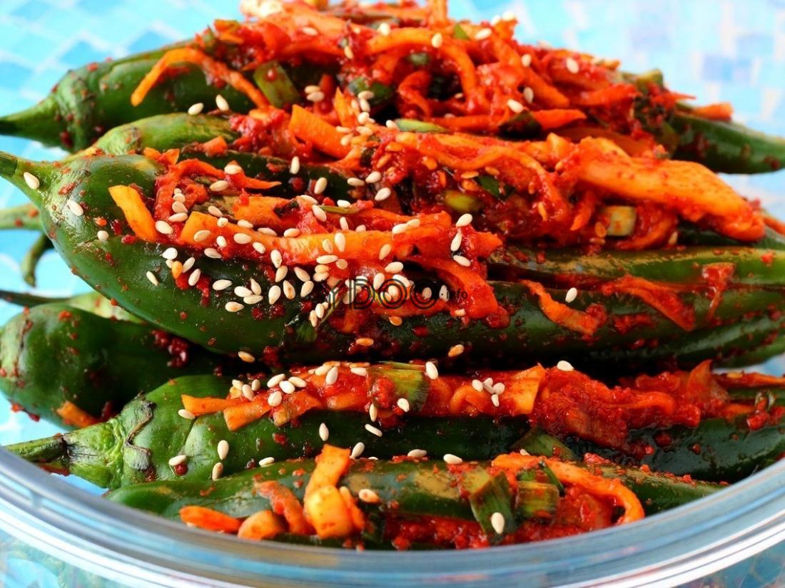 острый зеленый перец, начиненный овощной начинкой, в прозрачной стеклянной тарелке на столе, застеленном скатертью