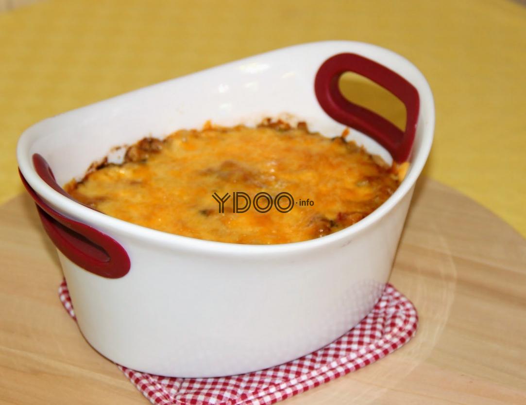 овощи, запеченные по итальянски по сыром, в белой форме для запекания на тканевой подставке на столе