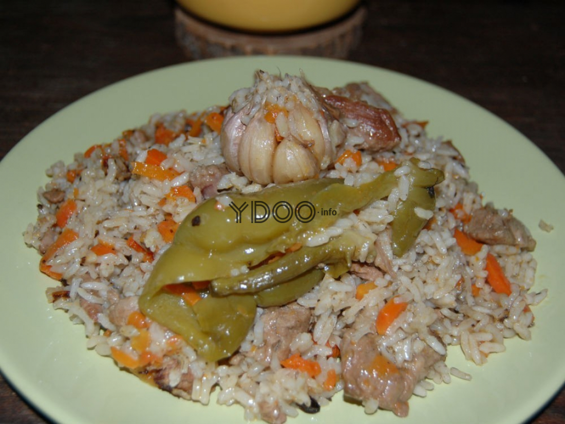 узбекский плов с кусочками баранины и морковью в тарелке на столе