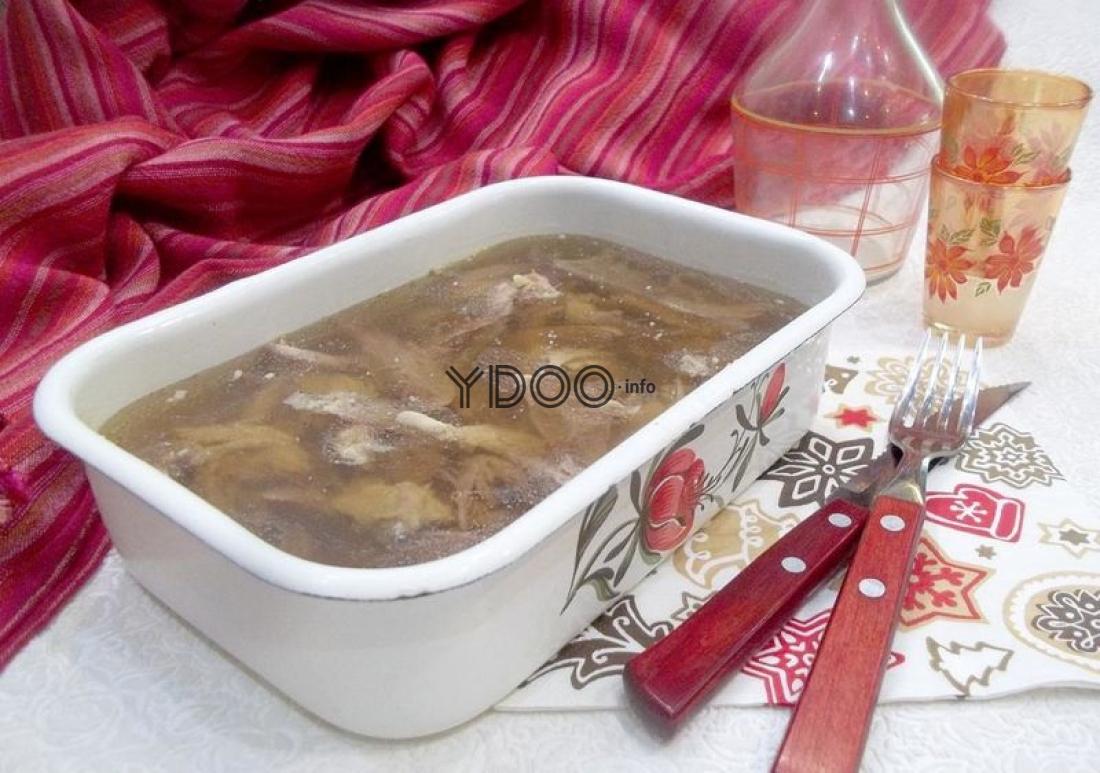 прозрачный холодец в судочке, рядом лежит столовый нож и вилка, рядом с судочком пустой графин и две рюмочки