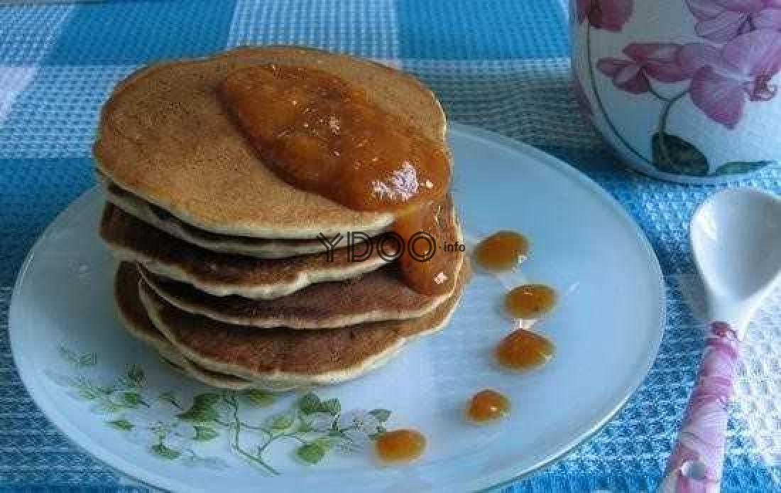 стопка ржаных оладий, политая абрикосовым вареньем, пластмассовая ложка и пиала с вареньем на столе, застеленном скатертью
