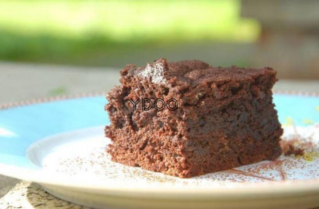 квадратный кусочек шоколадного брауни на маленькой белой тарелочке