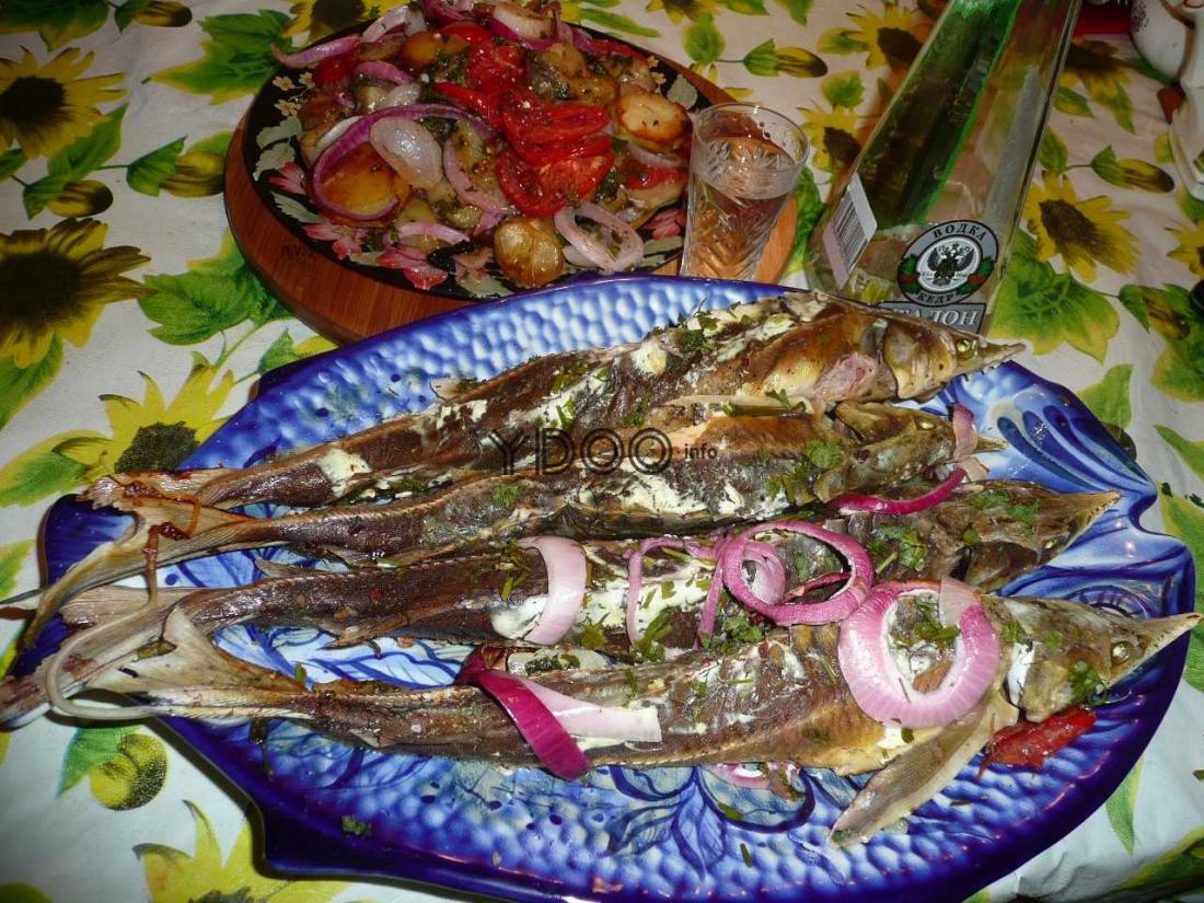 четыре рыбы стерляди лежат на тарелке, присыпанные свежей зеленью и репчатым луком, на большом блюде, рядом стоит рюмка и бутылка с водкой, деревянная доска на ней тарелка с запеченными овощами
