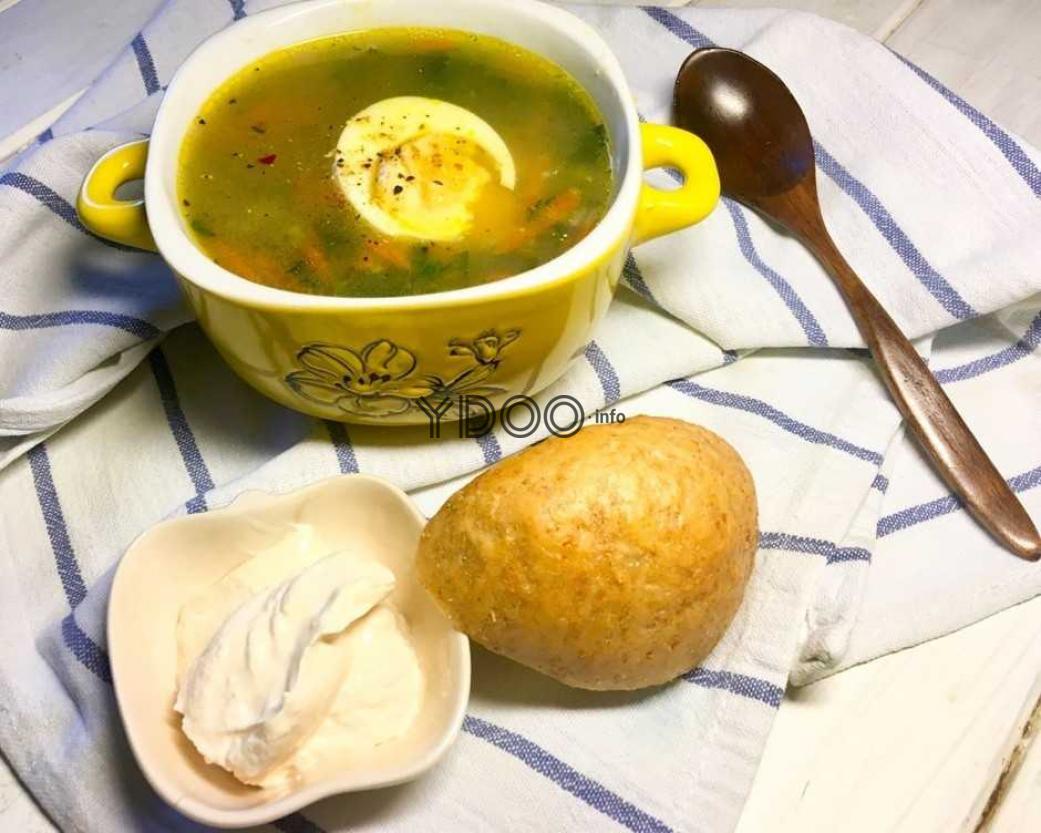 суп из крапивы, поданный с половиной вареного яйца, дополненный хлебом и сметаной