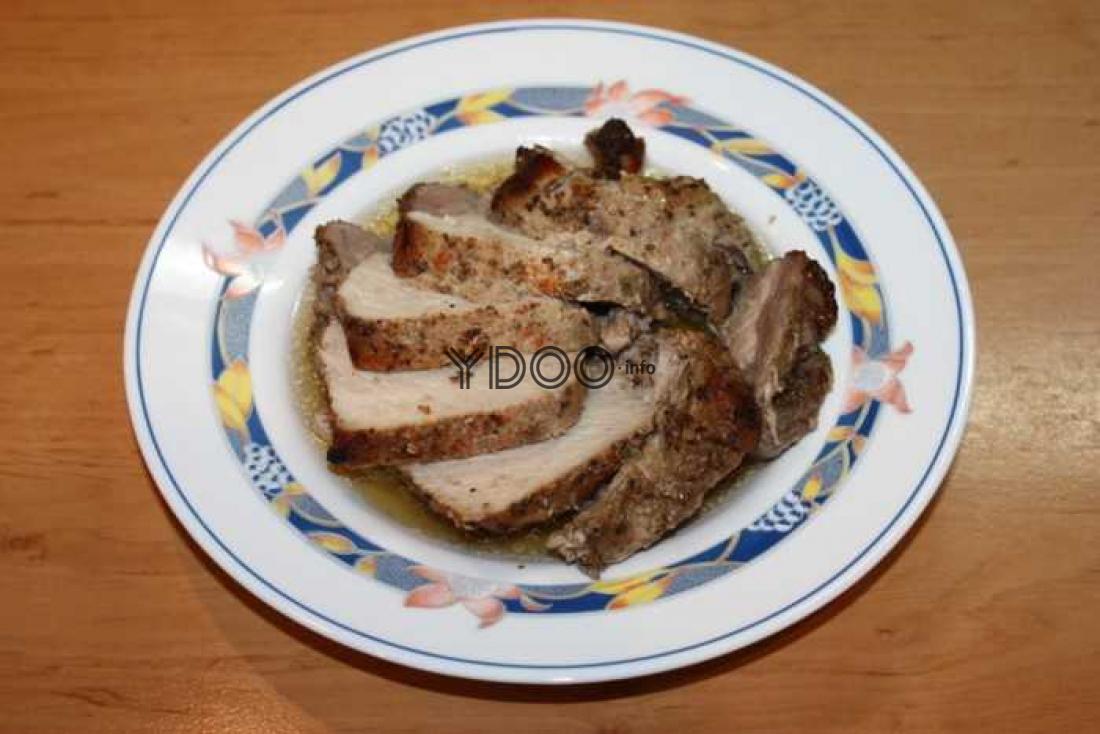 свинины, запеченная в фольге в духовке, нарезанная порционными кусочками, лежит на круглой белой тарелке с узорами