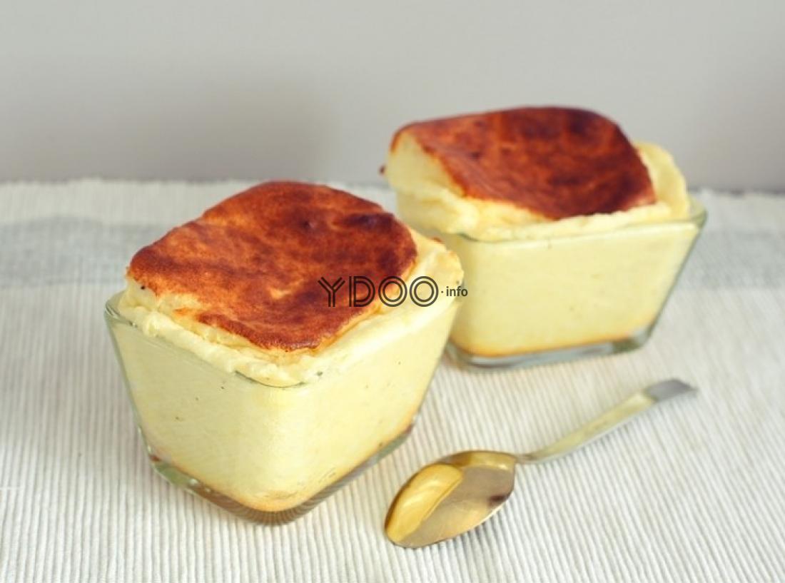 два сырных суфле в стеклянных формочках на столе, рядом ложка