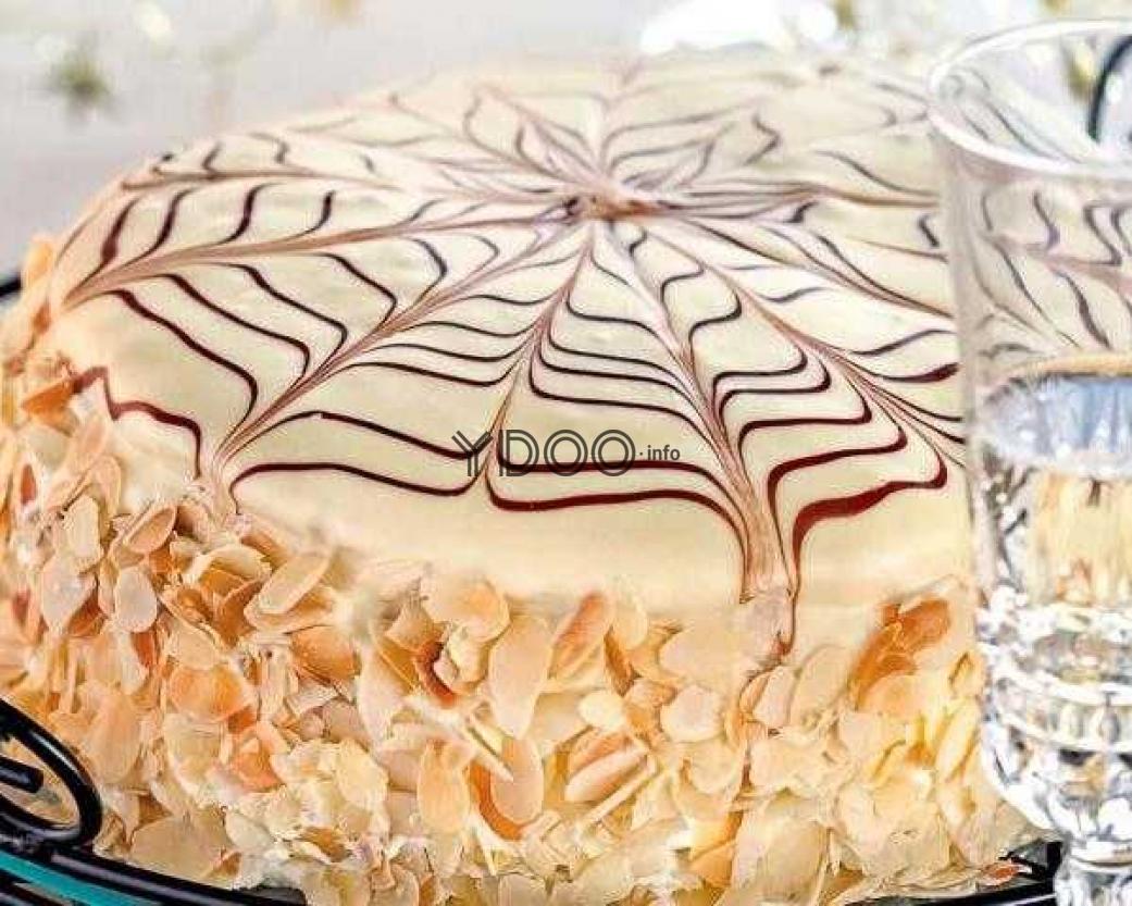 торт Эстерхази украшенный сверху белой и черной глазурью, по бокам присыпанный миндалем
