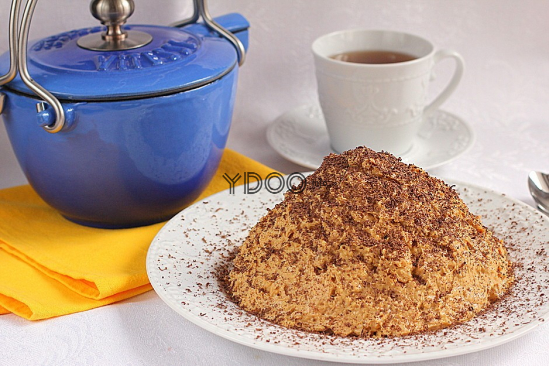 торт муравейник в виде горки на белой тарелке, рядом синий заварник на желтой салфетке и белая чашка с чаем