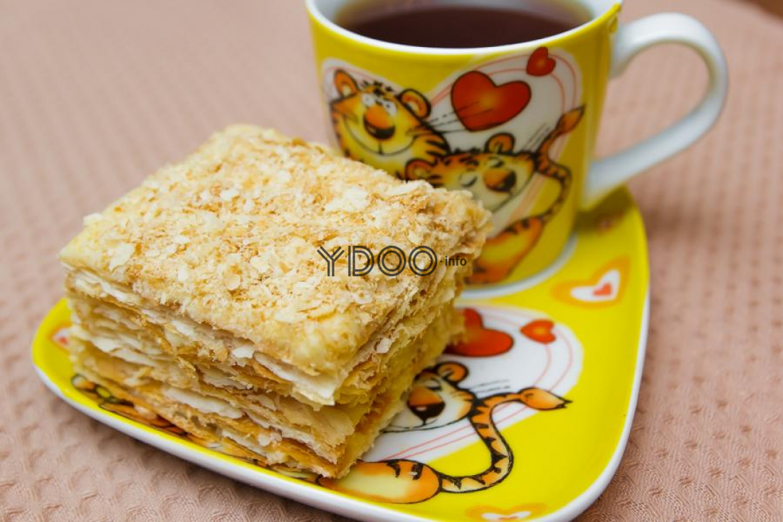 кусочек торта наполеона из готовых коржей на желтом блюдце с кружкой чая на столе, застеленном скатертью