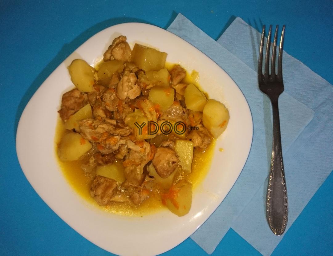 картошка тушеная с курицей в белой квадратной тарелке на столе